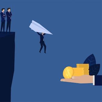 Бизнесмен падая с плоскостью бумаги для того чтобы получить метафору денег идти на риск.