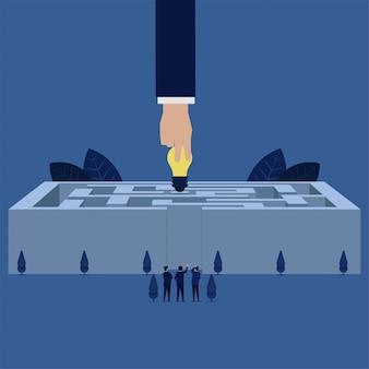 ビジネスの手は迷路チームの中心にアイデアを持ち、問題解決の意思決定の比喩を見たり作ったりします。