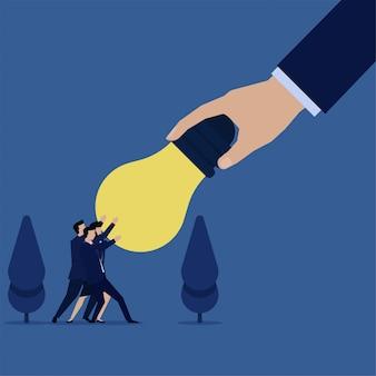 ビジネスチームは大きな手で盗まれてからアイデア電球を引っ張る