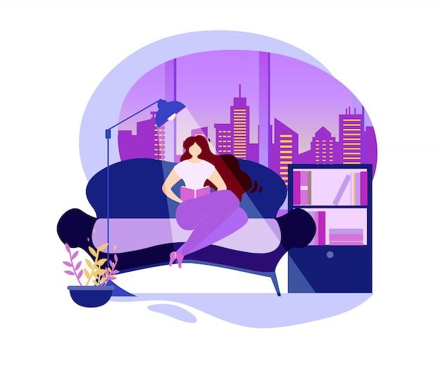 女性は窓の近くの快適なソファの上の本を読む