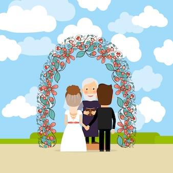 花のアーチの近くの結婚式