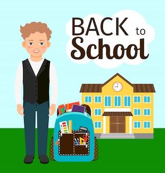 学校の前に立っているバックパックを持つ少年