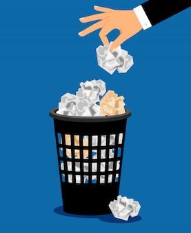 実業家の手がゴミ箱に紙を入れる