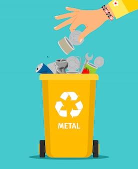 女性の手が金属製のゴミを投げます