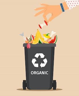 女性の手が有機ゴミを投げます