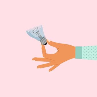 壊れた電球を持つ女性の手