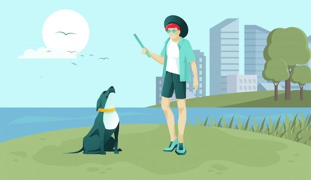 公園のフィールドでペットと遊ぶ若い犬の所有者