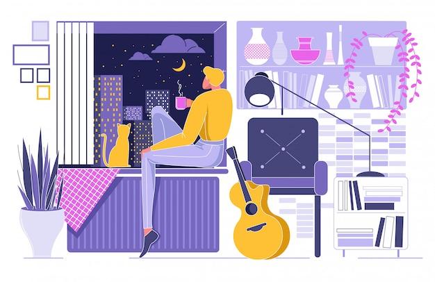 猫と街の夜に座っている男