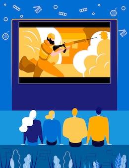 Люди смотрят фильм на экране в кинотеатре под открытым небом.