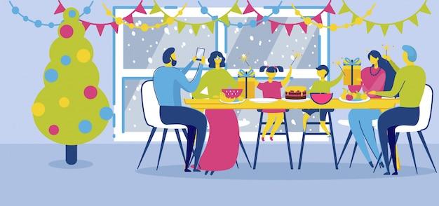 Счастливая семья, сидя за обеденным столом в канун рождества