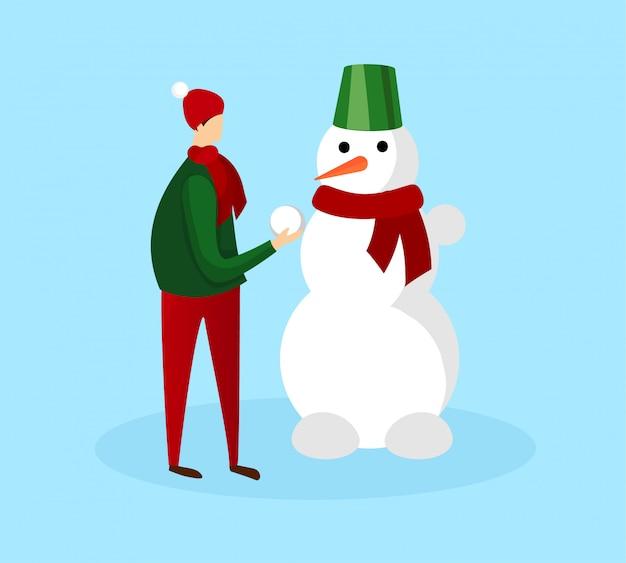 Подросток в теплой зимней одежде делает снеговика