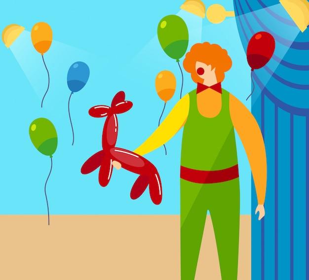 Клоун держит в руках красный шар в форме собаки