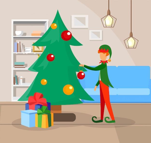 クリスマスツリーを飾るエルフのコスチュームの少年。