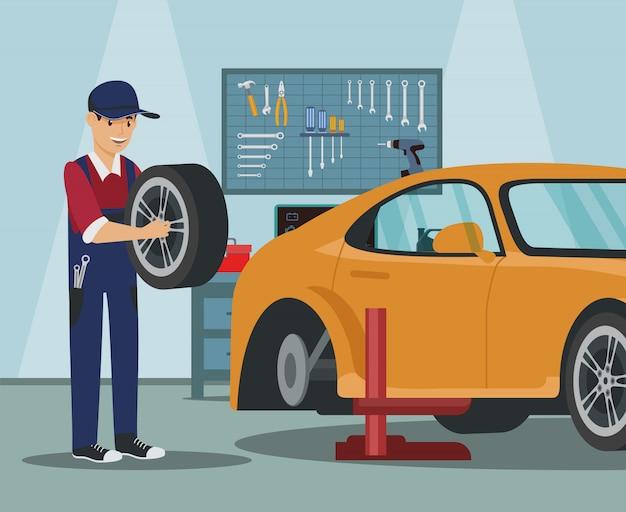 Рабочий с колесом в руке. замена автомобильных колес.
