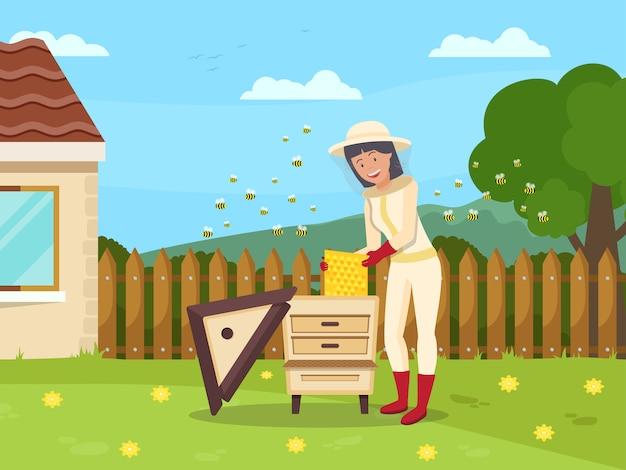女性の養蜂家はハイブからハニカムを引き出します