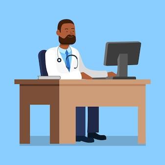 白衣の医者はコンピューターの近くのテーブルに座る。