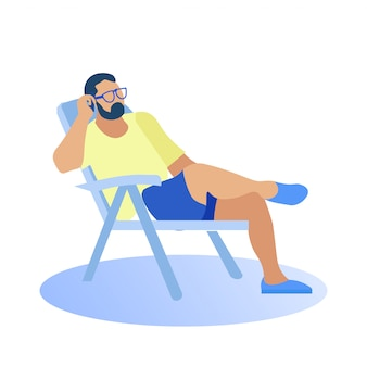 Человек в пляжной одежде сидит на стуле, разговаривает по телефону.