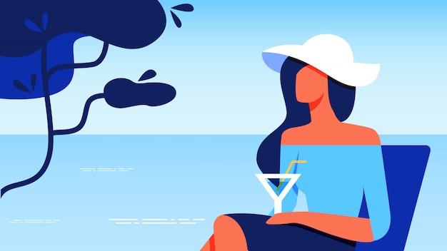 海のそばで休んでガラスと青いブラウスの女性。
