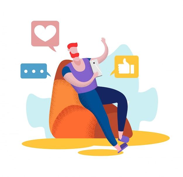 若い男がスマートフォンで自宅の肘掛け椅子に座る
