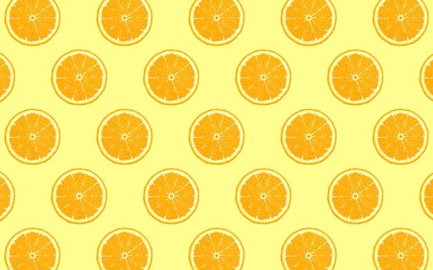 黄色の背景に新鮮なオレンジ半分のフルーツパターン。上面から