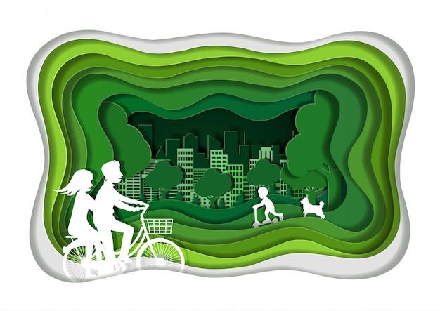 カップルはリラックスした休暇を楽しんでいる緑の芝生でサイクリングしています。緑豊かな街のコンセプトです。