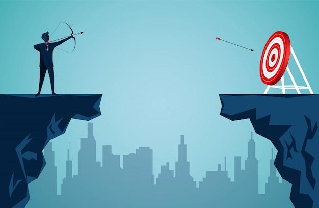 Бизнесмен, стоящий на скале, стреляет стрелой через скалу напротив стрелки к цели в центре красного круга