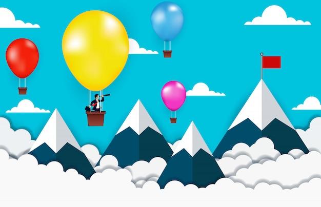 双眼鏡で見ているバルーンの上に立っているビジネスマンは山の間の空に赤い旗に行く