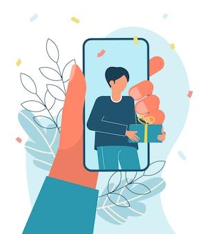 Онлайн вечеринка, день рождения, встреча друзей. человек дает подарок онлайн. телефон в руке.