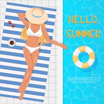 スイミングプールのそばのビーチタオルで日光浴の帽子の女。夏休みのコンセプトです。