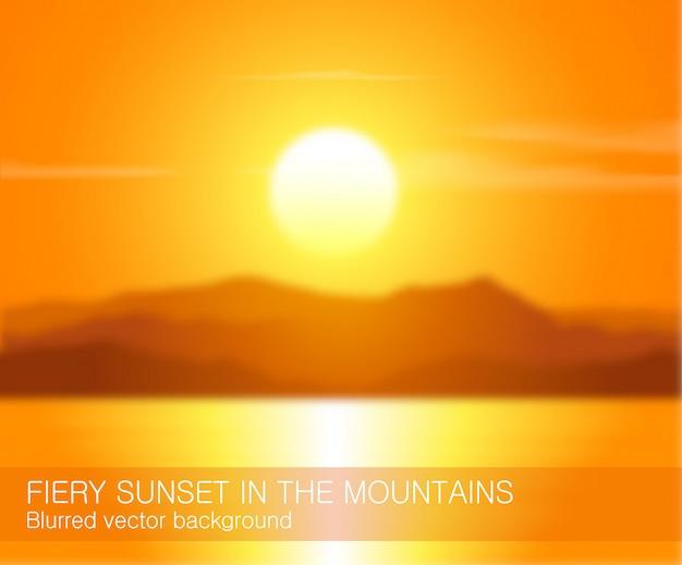山に沈む夕日とぼやけた風景。