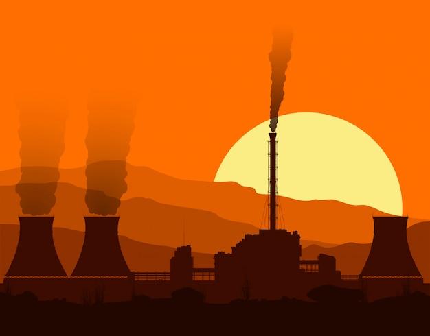 日没時の原子力発電所のシルエット。