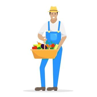 Фермер в спецодежде с корзиной с урожаем в руках.