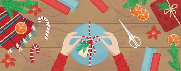 女の子はクリスマスプレゼントを詰め、弓を結びます。フラットのクリスマスイラスト。