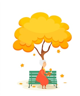 ベンチの老婦人。秋の黄色の木の下で本を読んで、公園のベンチで高齢者の女性。落ちてくるカエデの葉。秋の時間