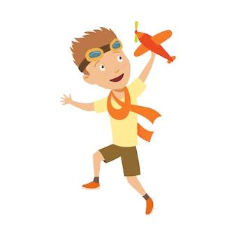 Маленький мальчик в костюме пилота мечтает о пилотировании самолета, играя с игрушками