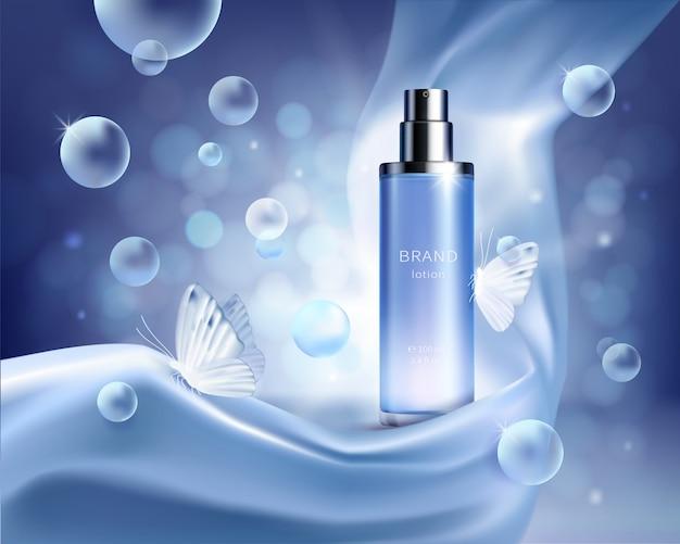 Голубая стеклянная бутылка-распылитель в складках шелковой ткани на синем фоне с пузырьками воздуха