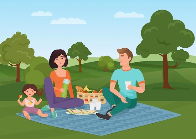 ピクニックに子供と一緒に幸せな若い家族。お父さん、お母さんと娘は自然の中で休んでいます。