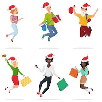 Набор счастливых молодых мульти этичных людей, подскакивающих, танцующих с подарочными коробками и рождественскими шляпами.