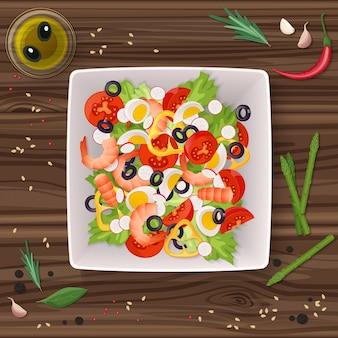 木製のテーブルに新鮮な野菜と緑の葉のサラダ皿。上面図。