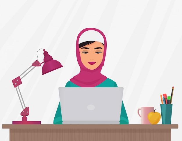 イスラム教徒の女性がラップトップに取り組んで