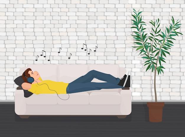 Человек лежал расслабиться на диване диван и слушать музыку.