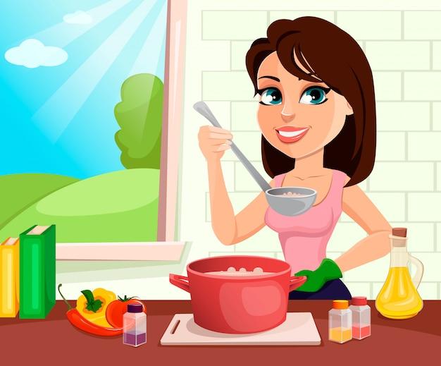 美しい女性が彼女の台所で料理をする