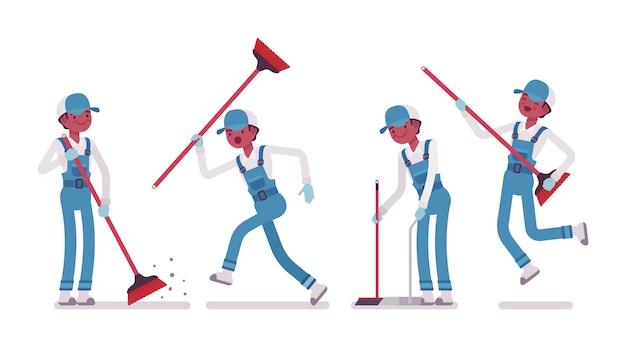 ほうきで床を掃除する男性用務員