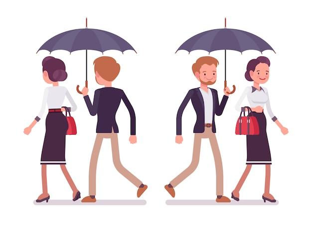 女性と紳士の傘、背面、正面の下で一緒に歩いて
