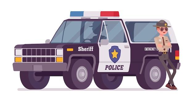車のバナー近くに立っている男性保安官