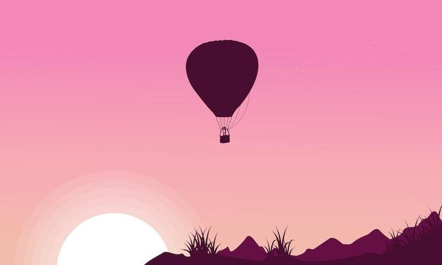ピンクの背景に熱気球のシルエット