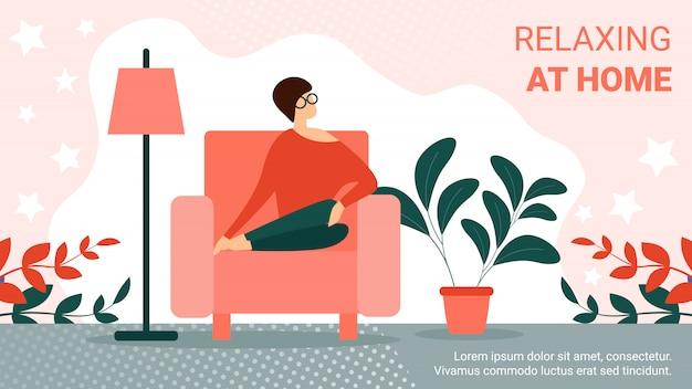 居間で居心地の良いアームチェアに座っている若い女性