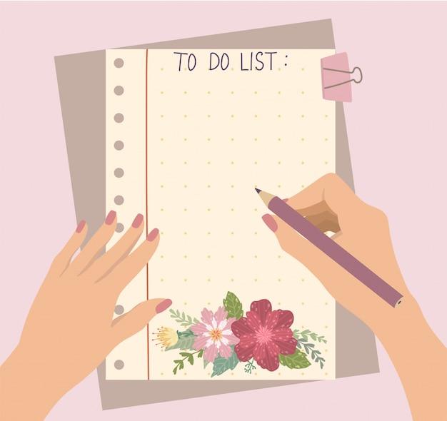 女性の手が美しい花のメモ帳で鉛筆を保持します。