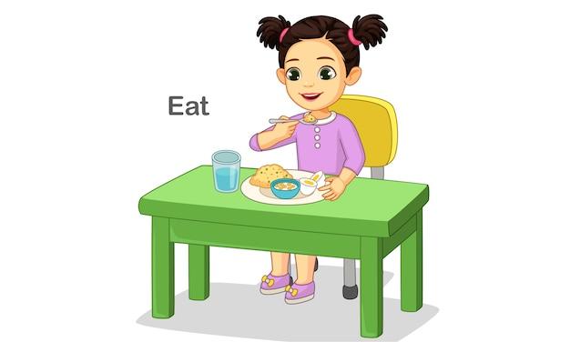 Милая маленькая девочка с удовольствием ест еду