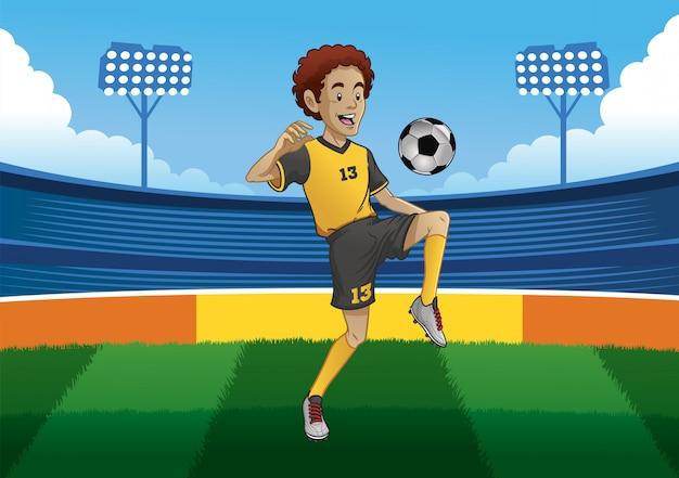 Футболист, жонглирующий мячом внутри на футбольном стадионе